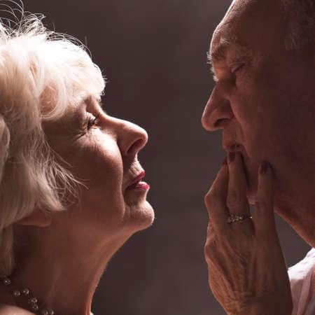 Elegant elderly woman caressing her senior husband