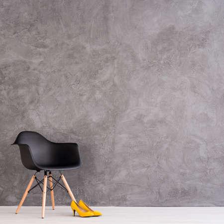 モダンな黒い椅子とセメントの壁の設計で広々 としたインテリアに立って黄色のハイヒール 写真素材
