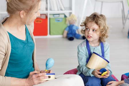 Young kindergarten teacher teaching little boy to play the music