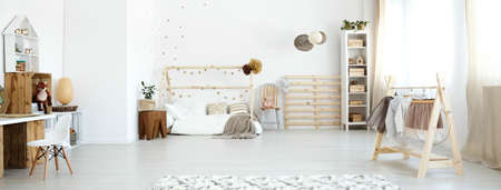 White scandi baby room with modern wooden accessories