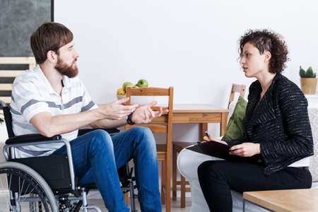 Jonge, bebaarde man in rolstoel praten met psychotherapeut thuis