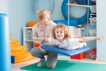 Happy boy lying on swing for vestibular therapy