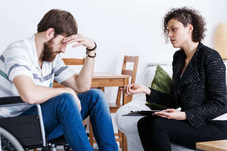 Huismedewerker die met depressieve ongeldige patiënt in rolstoel spreekt