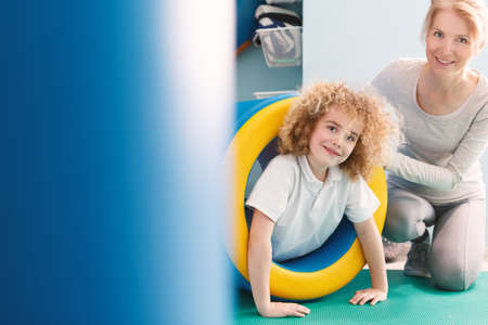 Physiotherapist and child in play tunnel exercising at sensory gym