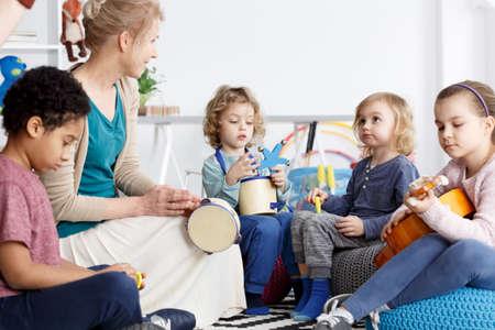 Vier kinderdagverblijven met plezier in de kleuterschool spelen de instrumenten