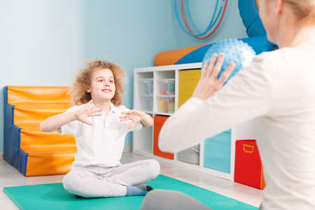 Child playing ball with physiotherapist during sensory integration session Stock Photo