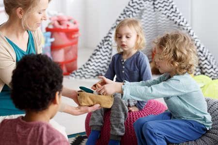 Kleine Kinder und ihre Lehrer-Reinigung Spielzeug nach dem Spiel