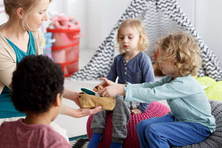Little kids and their teacher cleaning toys after play