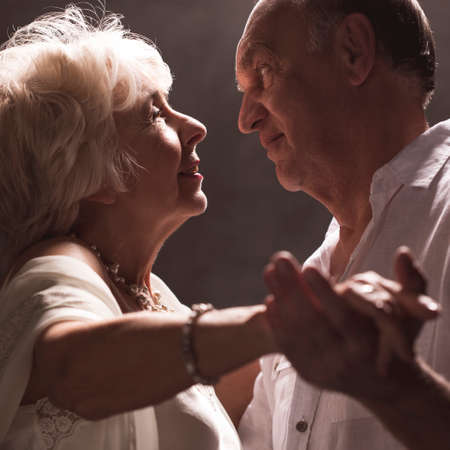 Happy senior woman and elderly man dancing during intimate moment