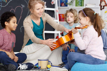 Little preschool girl holding teacher's guitar on music lesson Standard-Bild