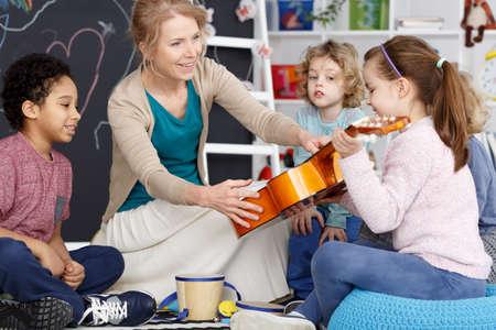 Little preschool girl holding teacher's guitar on music lesson Foto de archivo