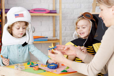 Little boy and girl dressed up on costume party in kindergarten