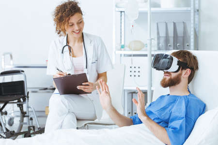 Young trauma patient wearing virtual reality glasses in hospital Banco de Imagens