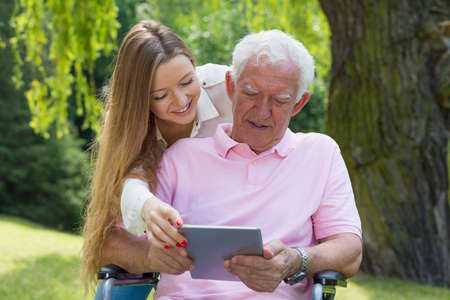 Young girl helping the senior man using the tablet