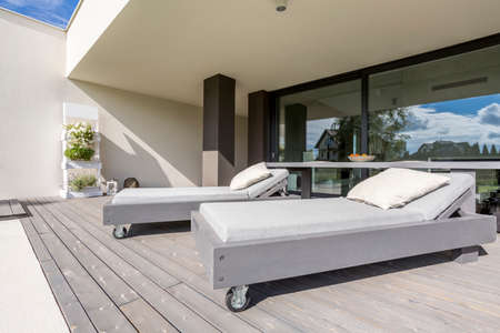 Luxurious mansion with sun lounger on terrace,