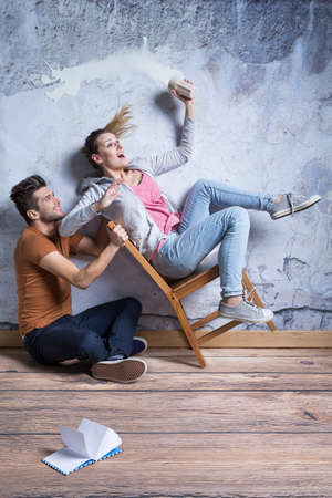 Overturning chair with young woman and man sitting on the floor