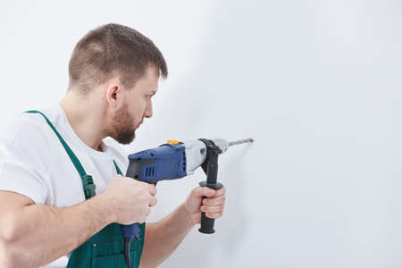 Worker is drilling in the wall during the renovation Stock Photo