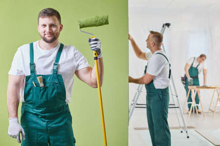 Renovation crew is  keeping a roller and painting the wall Stock Photo