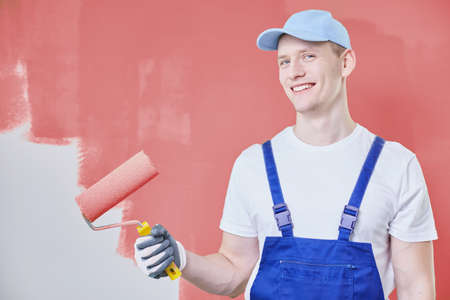 Painter wearing cap and overalls and standing against red wall with a paint roller