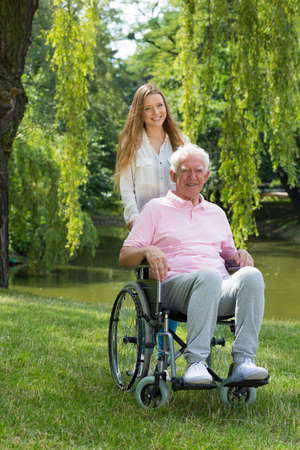 Young woman with elderly man on a wheelchair in the park Stock Photo