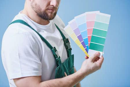 Jonge man staande tegen blauwe achtergrond met kleurstalen in zijn hand