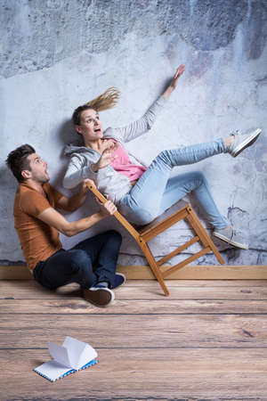Man catching the chair with scared young woman Reklamní fotografie