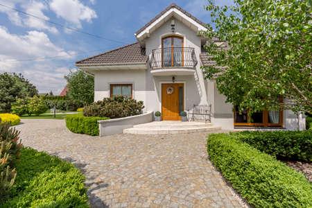 Mooi wit vrijstaand huis met tuin in de buitenwijken Stockfoto - 78814302