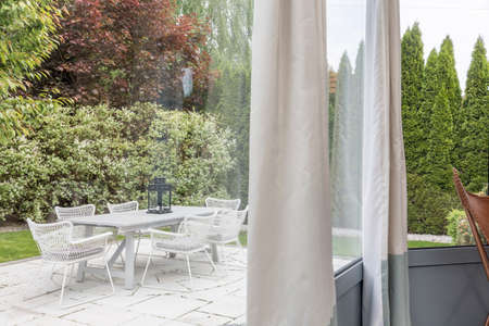 decoracion mesas: Beautiful terrace with elegant furnitures surrounded by garden