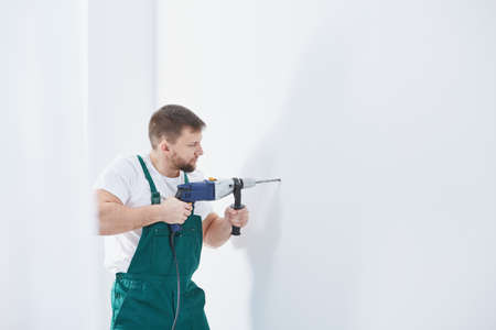 Worker is drilling in a wall during renovation Stock Photo