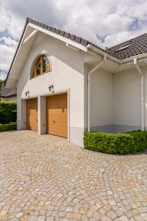 Paving stone driveway and two garages in detached house exterior