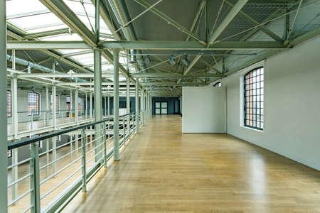 木製の床と旧工場のロフトの窓に白い壁