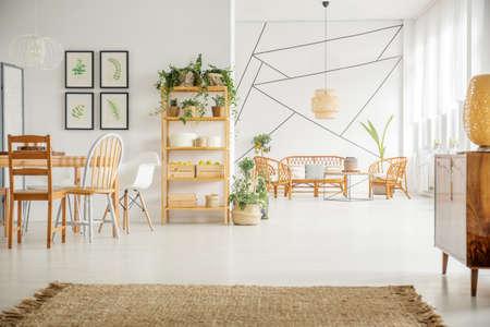 Licht appartement met houten tafel, stoelen, boekenplank en witte muren