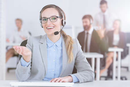 Positive hotline woman with glasses in bright office