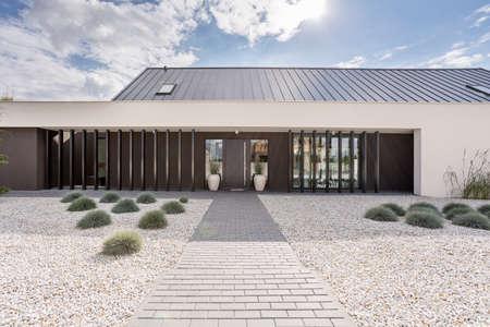 Villa backyard with stone path and white gravel
