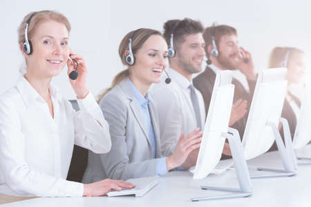 salespeople: Group of telemarketing workers with professional headsets Stock Photo