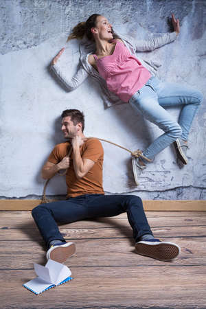 Man holding the line tied around womans leg