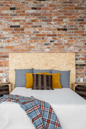 Cozy bedroom with red brick wall and wooden bed Stock Photo