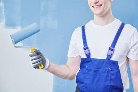 Gelukkige jonge huis schilder tegen de blauwe muur