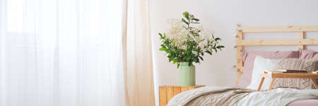 Cozy white and pink bedroom with wooden bed and flowers