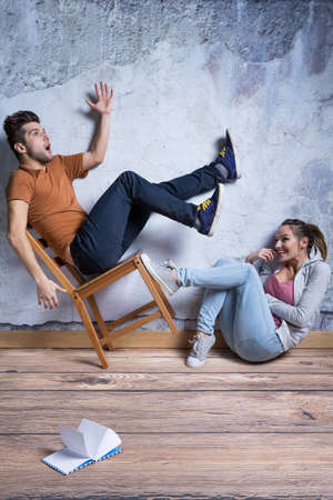 sit down: Girl sitting on the floor and bucking man from chair Stock Photo