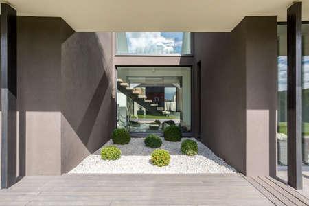 Buitenkant van moderne grijze villa met terras en groene installaties