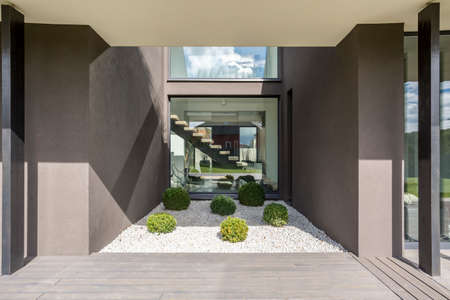Exterior of  modern grey villa with terrace and green plants Stok Fotoğraf
