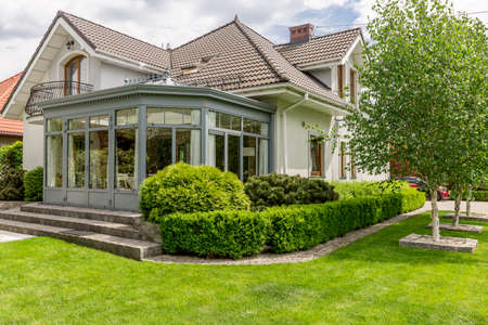 Foto de una casa moderna con cenador acristalado, cerca del jardín lleno de verde Foto de archivo - 78814303