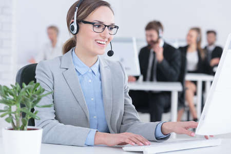 Positive elegant woman working in call center