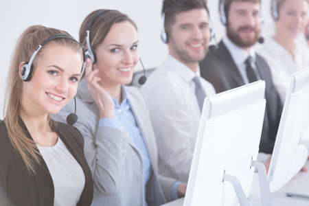 salespeople: Happy telemarketing consultants working in modern bright office