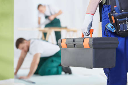 Le travailleur garde une boîte à outils et est prêt à rénover la salle Banque d'images - 78749949