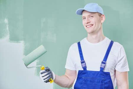 Jonge man die een verfrol houdt en een muur schildert