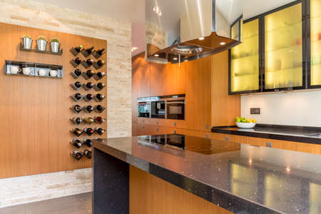 Glamourous kitchen with wooden cabinets and wine racks Stock Photo
