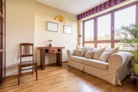 Gezellige woonkamer in natuurlijke kleuren met witte bank en koffietafel