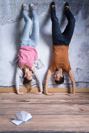 Smiled couple doing handstand in their room with book on the floor Reklamní fotografie - 78800932